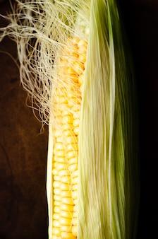 Gele maïskolf met bladeren en zijde