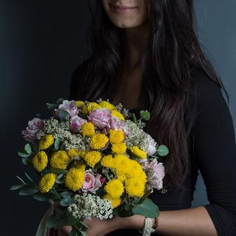 Gele margrieten en roze rozen gepromoot door een vrouw