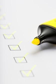Gele markering met markeringen op het controlelijstblad. checklist voltooid taakconcept.