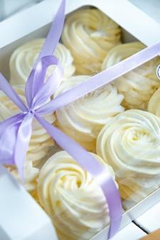 Gele marshmallow in een doos met een lint