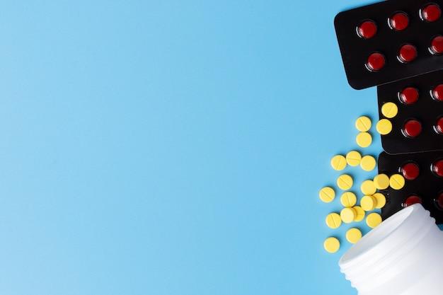 Gele medische pillen die uit witte fles en tabletten op blauwe achtergrond worden gemorst.