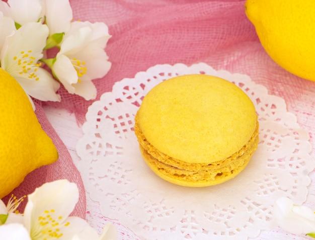 Gele meerlaagse koekjes macaron op een houten standaard met bloemen
