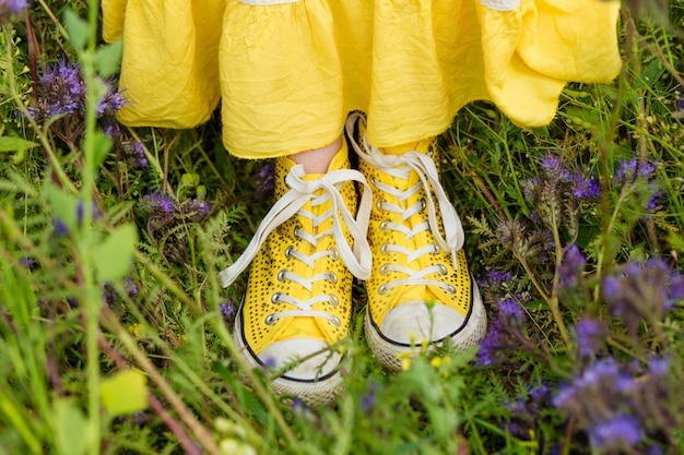 Gele meisjegymschoenen in het gras in de zomer