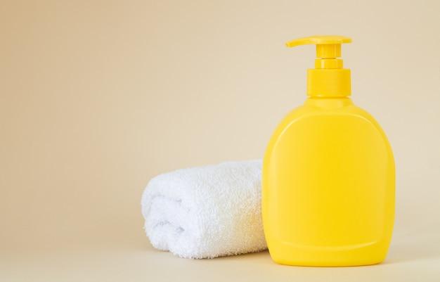 Gele merkloze dispenserfles met witte handdoek op beige achtergrond, verpakkingsmodel met kopie ruimte