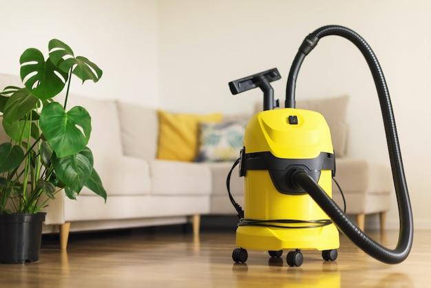 Gele moderne stofzuiger in de woonkamer. ruimte kopiëren. vlak schoon stofzuigconcept. groene monstera plant