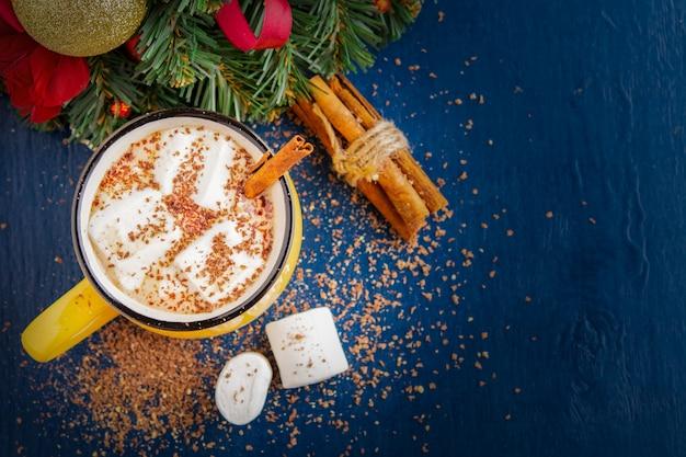 Gele mok met cacao of koffie op een donkerblauwe muur