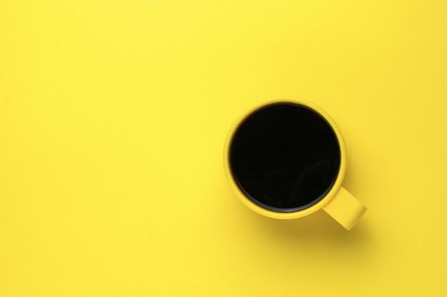 Gele mok met zwarte koffie op een gele achtergrond. een verkwikkend drankje. plat leggen.