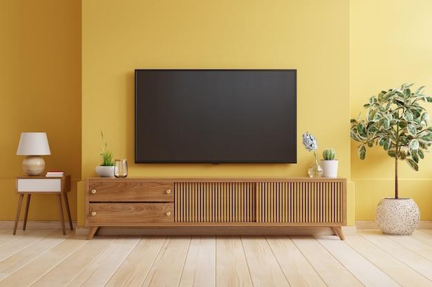 Gele muur achtergrond, tv is gemonteerd op een houten kast in een moderne woonkamer.3d-rendering