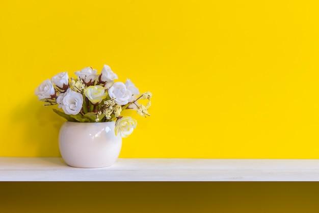 Gele muur met bloemen op planken wit hout, exemplaar ruimtetekst. stilleven concept
