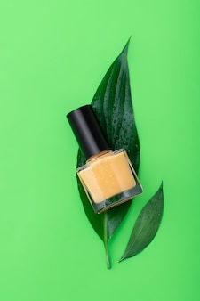 Gele nagellakfles op groen oppervlak.