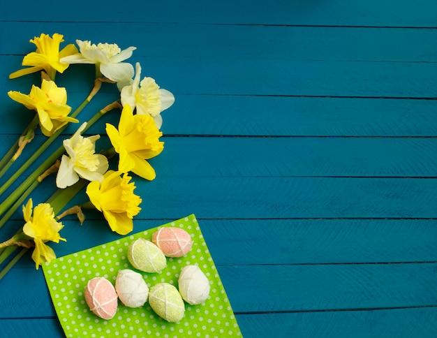 Gele narcissen en eieren op blauwe houten