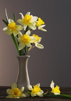 Gele narcissen in vaas op houten tafel op donkere achtergrond