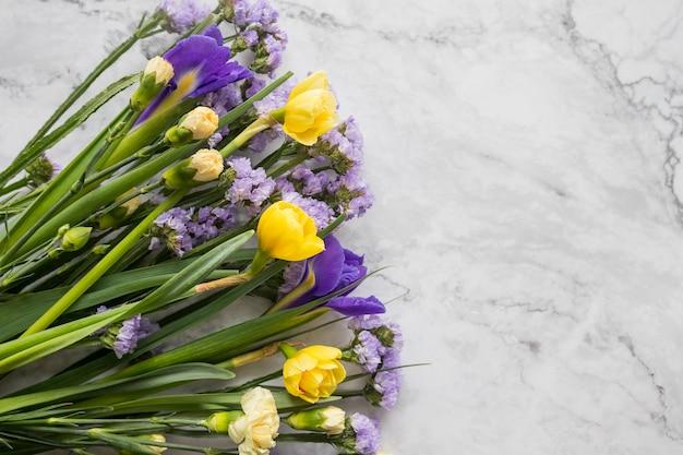 Gele narcissenbloemen en paarse irissen in een lijn bloemenregeling die op marmeren bloemen als achtergrond wordt geïsoleerd