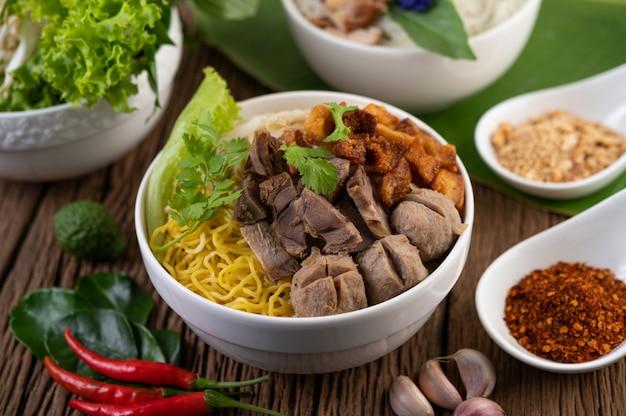 Gele noedels in een kopje met knapperig varkensvlees, plakjes varkensvlees en gehaktballen samen met thaise noedels in voedselstijl
