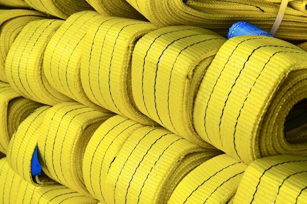 Gele nylon zachte hijsstroppen gestapeld in stapels. magazijn van afgewerkte producten voor industriële ondernemingen