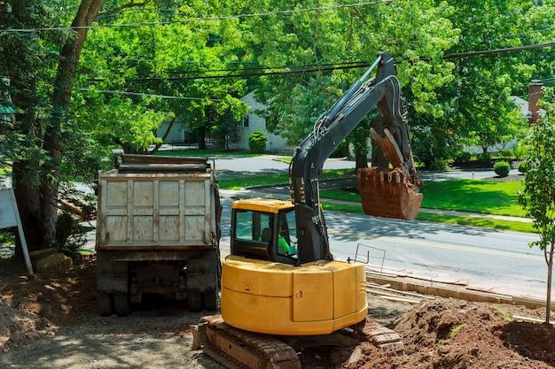 Gele op zwaar werk berekende graver die in uitgravingskuil werkt