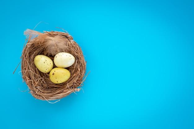 Gele paaseieren in een nest op een blauwe achtergrond.