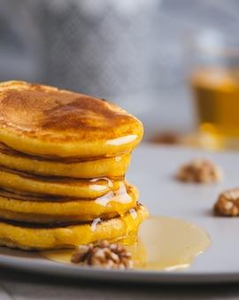 Gele pannenkoeken met maïsmeel en kurkuma, geklede honing en rode druiven. gezond ontbijt met superfoods. lichte achtergrond, knuffel scandinavische stijl.