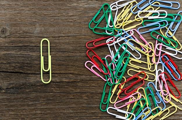 Gele paperclip gescheiden van groep kleurrijke