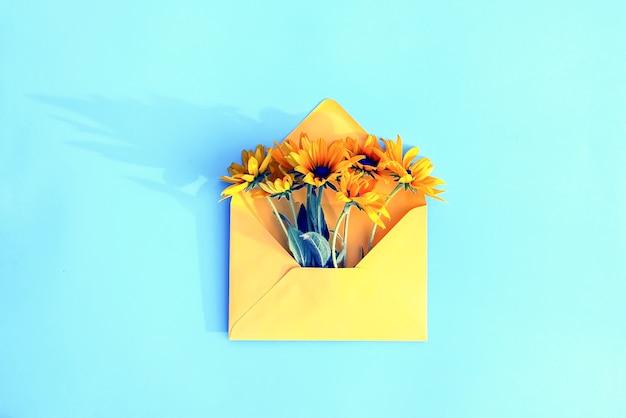 Gele papieren envelop met tuin rudbeckia bloemen op lichtblauwe achtergrond. feestelijke bloemen sjabloon. wenskaart ontwerp. bovenaanzicht. vintage-stijl. zwartogige susan plant.