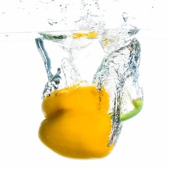 Gele paprika spatten in het water tegen een witte achtergrond