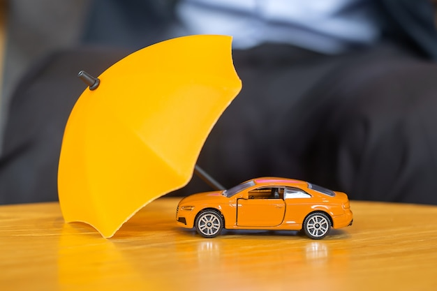 Gele paraplu dekking of bescherming oranje auto speelgoed op tafel