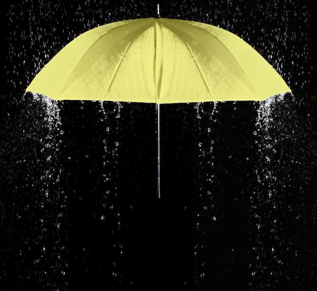 Gele paraplu onder regendruppels met zwarte achtergrond. bedrijfs- en modeconcept.