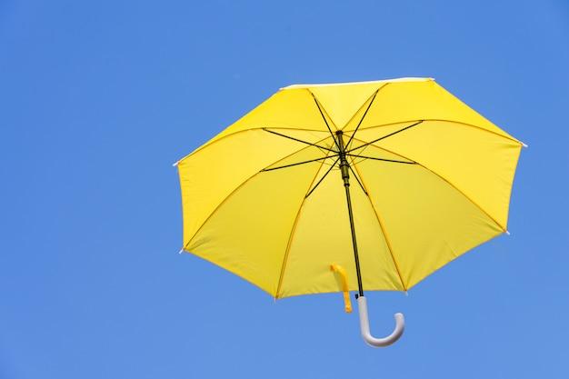 Gele paraplu's die in de hemel drijven