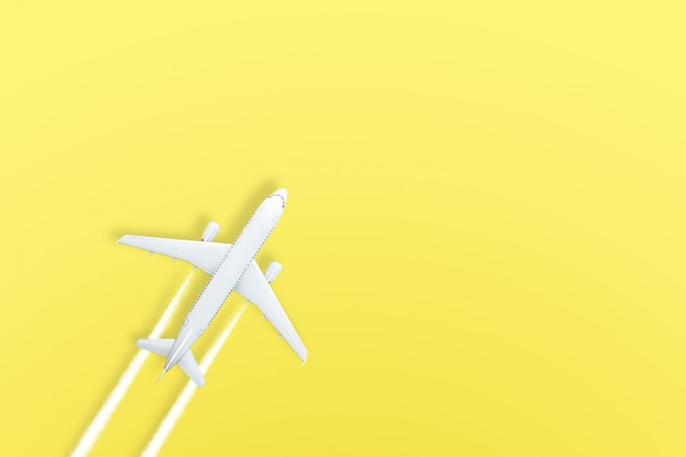 Gele pastel papieren vliegtuigje op geel
