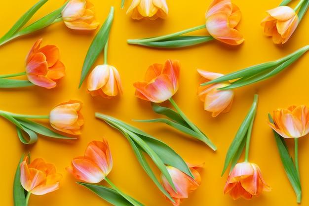 Gele pastelkleuren kleuren tulpen op de gele achtergrond. retro vintage stijl. stilleven, platliggende kunst.