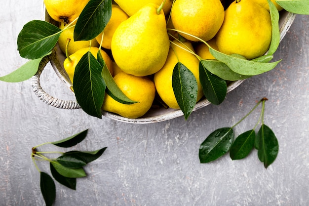 Gele peer in grijze mand op grijs oppervlak, oogst,