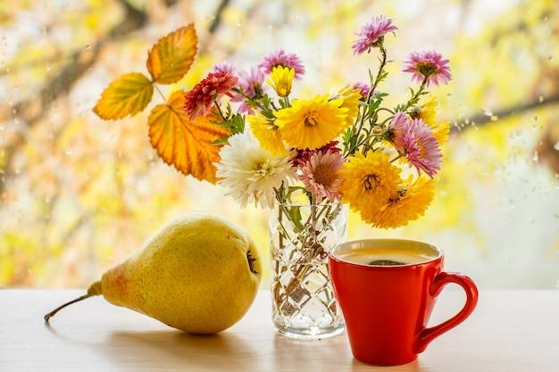 Gele peer, kopje koffie, bloemen en droog blad op vensterglas met waterdruppels in de wazige natuurlijke achtergrond.