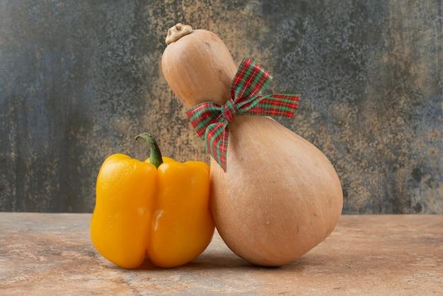 Gele peper en pompoen met strik op marmer