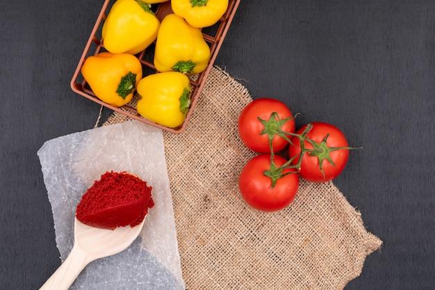 Gele peper in de mand in de buurt van een bos tomaten en tomatenpuree in lepel op zwart