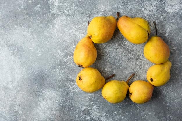 Gele peren in een cirkel op betonnen ondergrond.