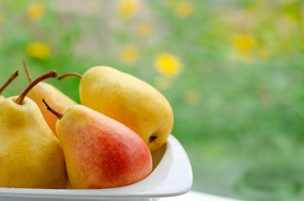 Gele peren op plaat op de venstermening op een zonnige dag.