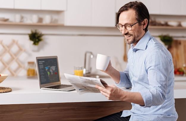 Gele pers controleren. begaafde creatieve glimlachende zelfstandige zakenman om thuis te zitten en sap te drinken tijdens het gebruik van gadget en het lezen van de krant