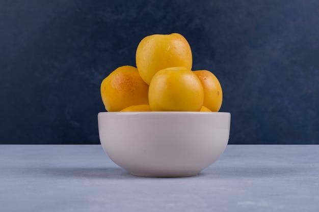 Gele perziken in een witte ceramische kom die op blauw wordt geïsoleerd