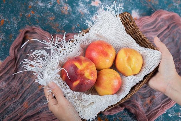 Gele perziken op een witte rustieke keukenhanddoek.