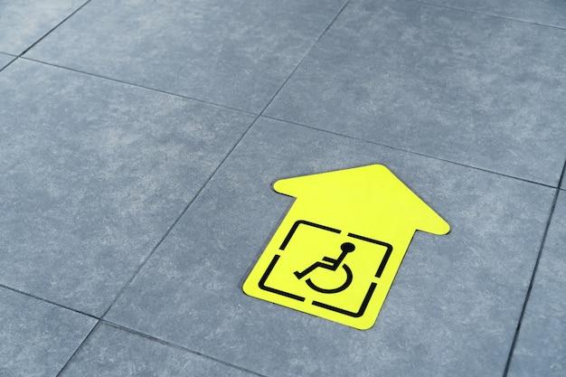 Gele pijl voor gehandicapten op de tegel van de wachtkamer op de luchthaven.