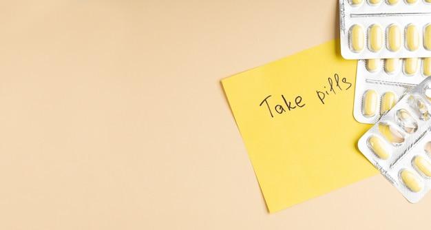 Gele pillen in blister en post-it om pillen op gele achtergrond te nemen