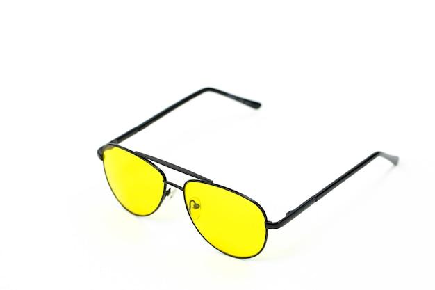 Gele piloot bril in zwart frame geïsoleerd op een witte muur