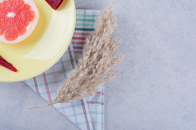 Gele plaat van droog fruitpulp en grapefruit op steen.