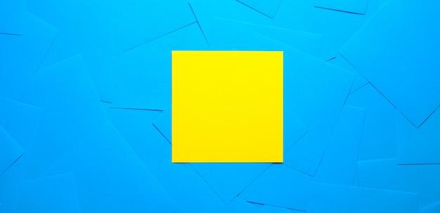 Gele plakkerige sticker voor informatieherinnering. ruimte voor tekst. ernaast zijn lege blauwe stickers. banier