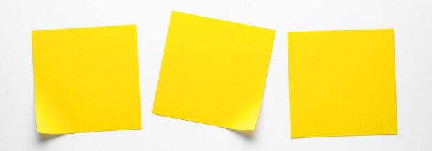 Gele plakkerige stickers op een witte achtergrond om u te herinneren aan informatie. ruimte voor tekst. banier