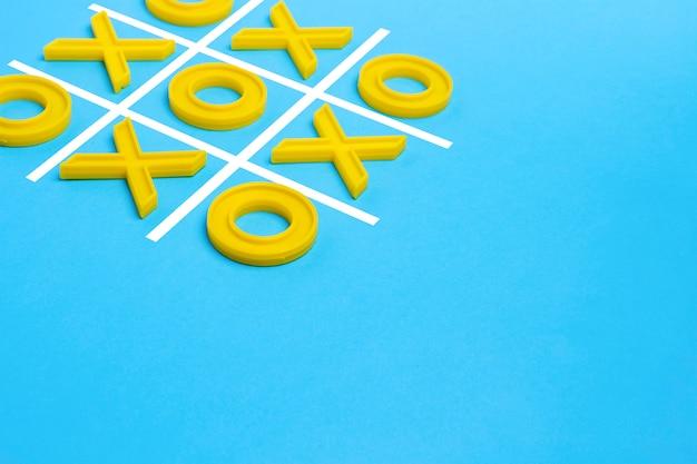 Gele plastic kruisen en een teen en een geregeerd veld voor het spelen van tic-tac-toe op een blauw oppervlak. concept xo win challenge. educatief spel voor kinderen