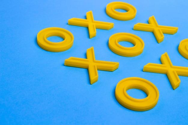 Gele plastic kruisjes en nullen voor het spelen van tic-tac-toe op een blauw oppervlak. concept xo win challenge. educatief spel voor kinderen