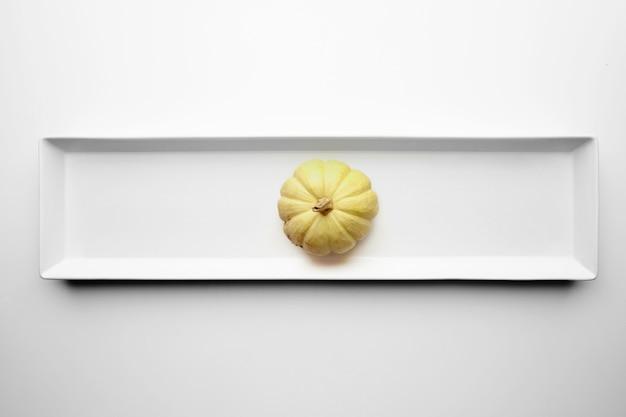 Gele pompoen die in centrum van ceramische rechthoekige plaat op witte achtergrond wordt geïsoleerd