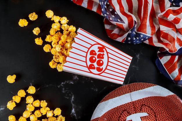 Gele popcorn in gestreepte dozen die op zwarte oppervlakte met amerikaanse voetbalplaat worden gemorst