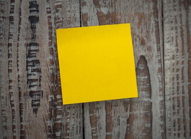 Gele post-it geplakt op een muur